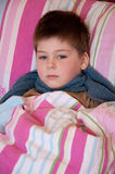 Sick boy lying in bed Stock Images