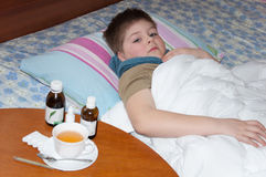 Sick boy lying in bed. Stock Image