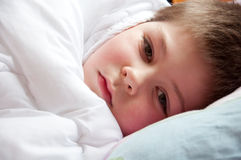 Sick boy lying in bed Stock Photography