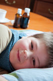 Sick boy lying in bed Royalty Free Stock Image