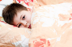 Sick boy lying in bed Stock Photos