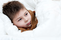 Sick boy lying in bed Royalty Free Stock Photography