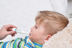 Sick boy lying in bed with a thermometer in mouth Stock Photo