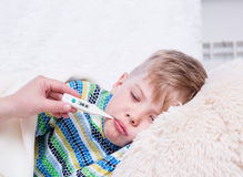 Sick boy lying in bed with a thermometer in mouth Royalty Free Stock Images