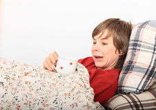 Sick boy. Mad kid lying in a bed on pillows under blanket with flowers and drinking cup of tea Royalty Free Stock Photography