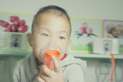 Sick boy making atomization treatment Royalty Free Stock Photo