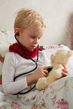 Sick boy is playing with a stethoscope stock image