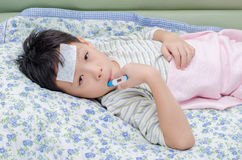 Sick boy on sofa with thermometer in mouth Stock Images