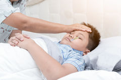 Sick boy with thermometer laying on bed and mother hand taking t stock image