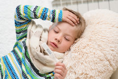 Sick boy with thermometer laying in bed and taking temperature Royalty Free Stock Images