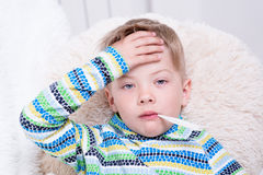 Sick boy with thermometer laying in bed and taking temperature Royalty Free Stock Photography