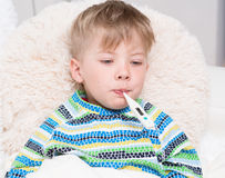 Sick boy with thermometer in mouth laying in bed Royalty Free Stock Images