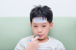 Sick boy with thermometer in mouth Royalty Free Stock Images