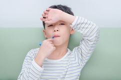 Sick boy with thermometer in mouth Stock Photos