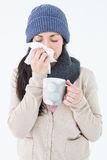 Sick brunette blowing her nose while holding a mug royalty free stock photography