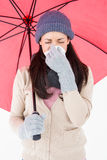 Sick brunette blowing her nose while holding an umbrella Royalty Free Stock Image