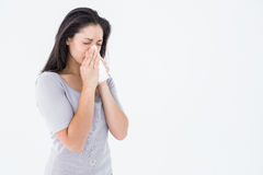 Sick brunette blowing her nose Royalty Free Stock Photography