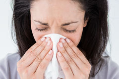 Sick brunette blowing her nose Stock Image