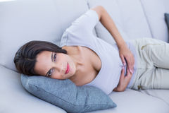 Sick brunette having stomachache Stock Photos