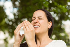 Sick brunette holding tissue sneezing Royalty Free Stock Photos