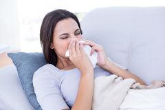 Sick brunette lying on the couch and blowing her nose Royalty Free Stock Photography