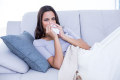 Sick brunette lying on the couch and blowing her nose Stock Photo