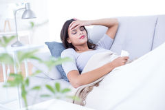 Sick brunette lying on the couch Stock Image