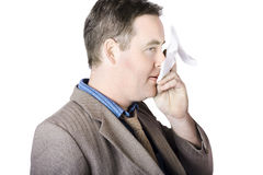 Sick business man with cold and flu cough. Isolated picture of a sick business man sneezing into tissue with cold and flu cough Stock Photos
