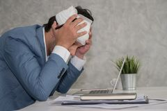 Sick business man touching his head with hands while using lapto royalty free stock image