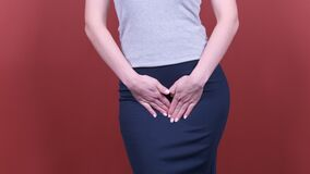 Sick business woman with hands holding pressing her crotch lower abdomen. Medical or gynecological problems, healthcare