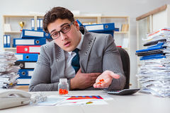 The sick businessman with medicines at work desk Stock Photo
