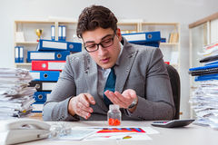 The sick businessman with medicines at work desk Stock Photography