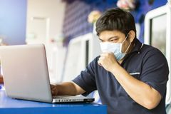 Sick businessman use laptop computer with temperature and headache working in office. Asian man wearing a face mask with coughing royalty free stock photo
