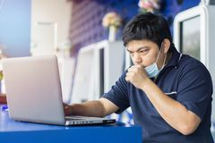 Sick businessman use laptop computer with temperature and headache working in office. Asian man wearing a face mask with coughing stock photos