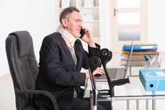 Sick businessman at work. Businessman at work wearing neck brace with crutches royalty free stock image