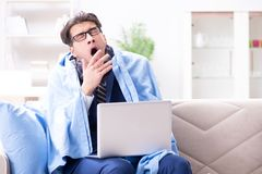 The sick businessman working from home due to flu sickness. Sick businessman working from home due to flu sickness Stock Photo
