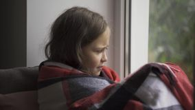 Sick caucasian child covered with a warm blanket sitting on windowsill at home. Little brunette girl with fever looking. At the window sadly. Concept of health stock video
