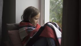 Sick caucasian girl covered in blanket sitting on windowsill at home. The child has fever, she is cold. Concept of. Health, illness, sickness, common cold stock footage