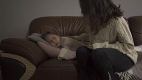 Sick caucasian girl lying under blanket at home. Sad child has fever. Young mother checking daughter`s temperature on. Sick caucasian girl lying under blanket at stock video
