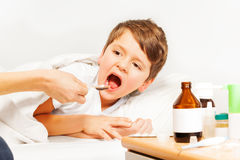 Sick Caucasian kid boy taking meds laying in bed. Sick Caucasian kid boy taking meds laying in  bed of hospital ward with blanked background Stock Photo