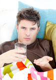 Sick caucasian man holding pills and water on sofa Royalty Free Stock Photos
