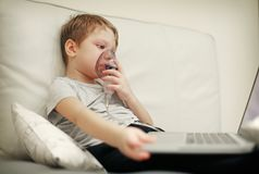 Sick chid with pediatric nebulizer mask in front of laptop. Little kid with asthma or bronchitis has trouble breathing. Ill boy entertaining himself by Royalty Free Stock Photos
