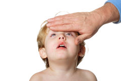 Sick Child. A parents hand rests on a sick childs forehead checking for fever Royalty Free Stock Photography