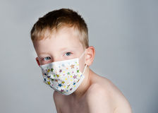 Sick Child. Or child around sick peoples germs.  Young boy is wearing a children's germ or flu mask, also used for allergies or dust.  Plain grey background Royalty Free Stock Photos