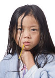 Sick Child. A young asian girl with a thermometer  not feeling very well Royalty Free Stock Image