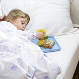 Sick child. Young girl lying in bed with flu Royalty Free Stock Images