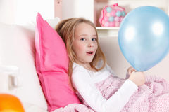Sick child with a balloon. Happy sick child with a balloon in the bed Stock Photo