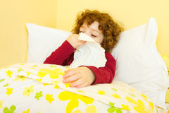 Sick child in bed. Curly haired little sick girl laying in bed and blowing her nose Stock Photography