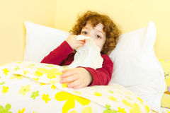 Sick child in bed blowing her nose. Curly haired little sick girl laying in bed and blowing her nose Stock Images