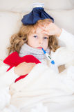 Sick child in bed. Sick child with fever and hot water bottle at home Royalty Free Stock Photography